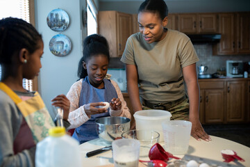 Army soldier mother teaching daughters how to bake in kitchen