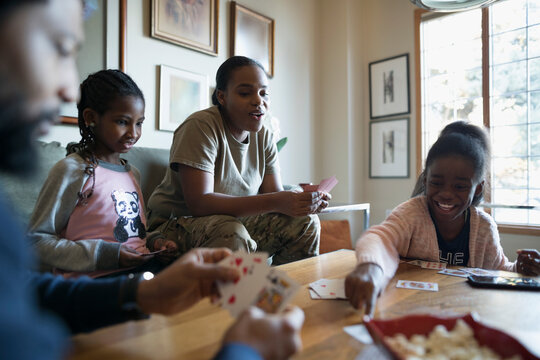 Family playing cards at coffee table
