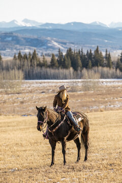 Female rancher horseback riding on sunny mountain ranch