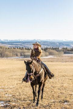 Female rancher horseback riding on sunny ranch