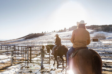 Girl opening gate for ranchers horseback riding in sunny snowy paddock