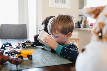 Young boy drinking milk from cereal bowl