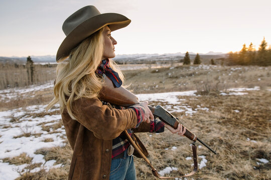 Female hunter with rifle in snowy field at sunset