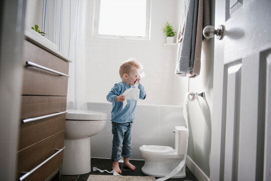 Boy blowing nose on toilet paper