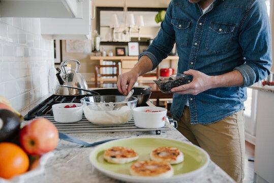 Man making pancakes in kitchen