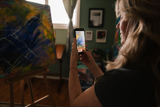 Woman photographing artwork on phone