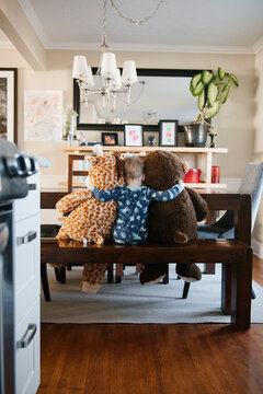 Rear view of boy playing on bench with soft toys at home