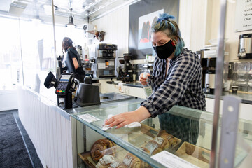 Female worker in face mask spray cleaning cafe counter