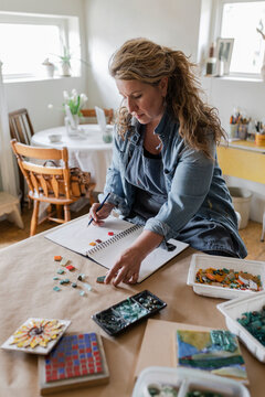 Female artist sketching ideas for mosaic in home art studio