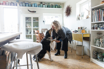 Female artist kissing dog in home art studio