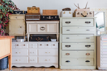Dressers and trunks stacked in art studio