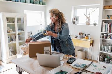 Female artist taping package for e-commerce in home art studio