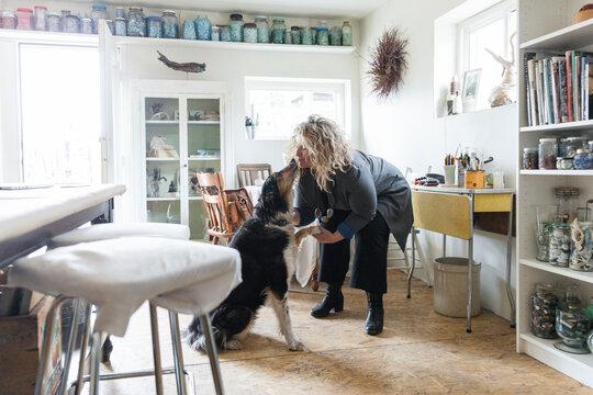 Female artist kissing dog in home art studio