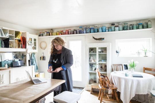 Female artist using smart phone at laptop in home art studio