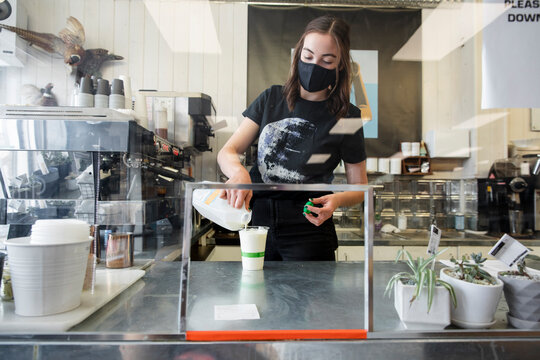 Female barista in face mask working behind sneeze guard in cafe