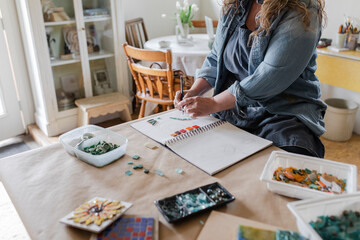Female artist planning mosaic project in home art studio