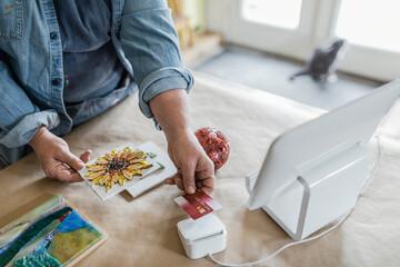 Close up female artist with mosaic using credit card swiper