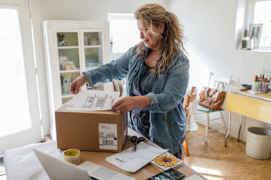 Female artist placing shipping label on box in home art studio