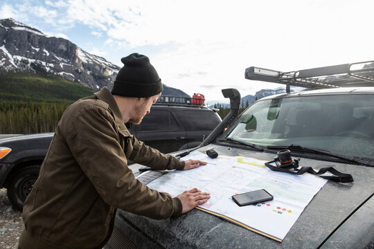 Man with map planning at overland SUV below mountains
