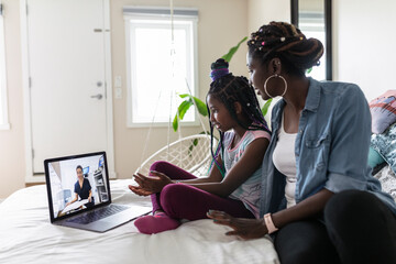 Mother and daughter video chatting with teacher on laptop in bedroom