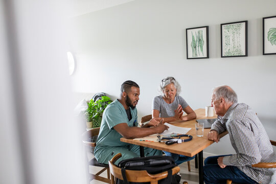 Home caregiver meeting with senior couple at kitchen table