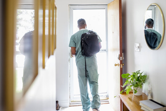 Male nurse in scrubs with backpack leaving house for work