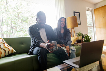 Happy couple using laptop in living room