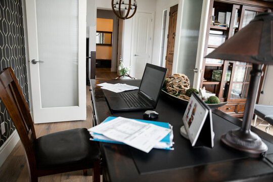 Paperwork and laptop on desk in home office