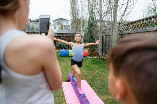 Preteen girl posing for photograph on gymnast mat in garden