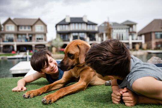 Portrait of brothers with pet dog in garden by waterside