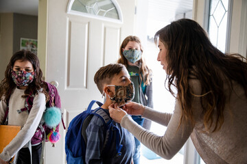 Mother assuring son wearing face mask