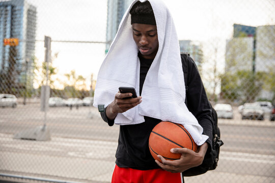 Young man with towel and smart phone on urban basketball court