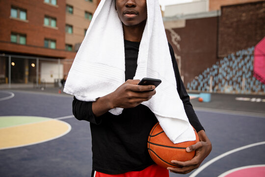 Close up young man with towel and smart phone on basketball court