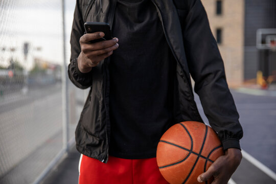 Close up young man with smart phone and basketball