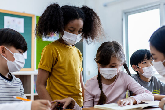 Diversity of children students wearing medical masks in the classroom.