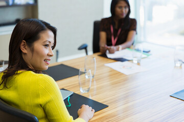 Smiling businesswoman listening in conference room meeting