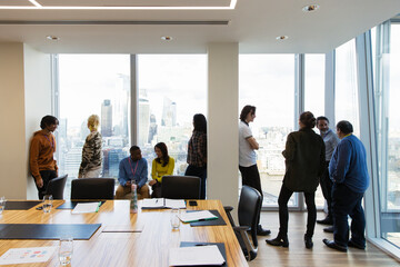 Business people talking at highrise conference room windows