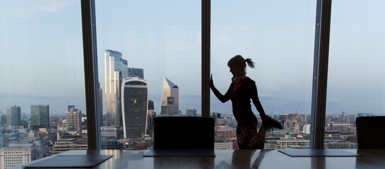 Businesswoman stretching at highrise office window, London, UK