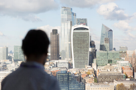 Businessman looking at sunny London cityscape from office window, UK