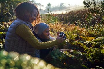 Happy hiking couple using camera among sunny ferns and undergrowth