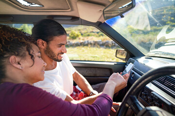 Young couple using smart phone on road trip in sunny car
