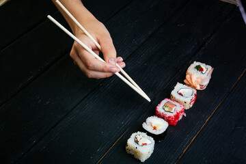 Female hand takes sushi rolls with Chinese chopsticks. Lying on a black wooden board. Lying on a black wooden board. View from above