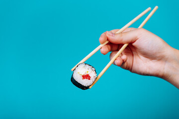 Woman's hand holds tasty sushi roll maki with wooden chopsticks on blue background. Place for caption and text