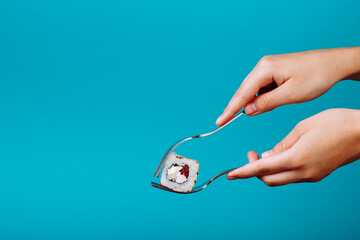 Hand holding fresh California sushi roll with a fork, isolated on blue background. How to eat sushi without chopsticks