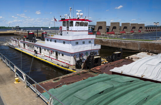 Pushing Barges:  A towboat moves three rows of covered barges through a lock and past a dam on the Mississippi River.