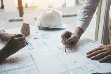 Engineering man showing blueprint detail for people buying house. - fototapety na wymiar