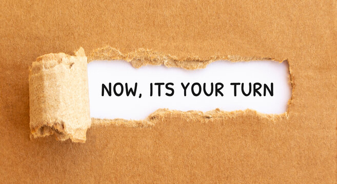 Text Now, Its Your Turn appearing behind torn brown paper