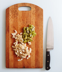 Fresh cut of banana and kiwi on wooden chopping board with knife. isolated on white, from above, flat lay