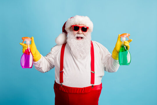 Portrait of his he nice attractive cheerful cheery glad overweight Santa cleaning up holding in hands supplies chemical isolated bright vivid shine vibrant blue color background