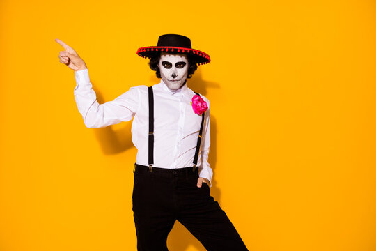 Photo of creepy guy direct finger empty space hand pocket show danger promotion wear white shirt rose death costume sugar skull sombrero suspenders isolated yellow color background